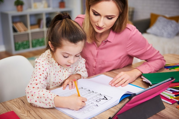 Mujer joven, ayudar, niña, con, tarea
