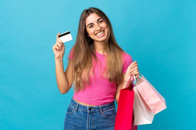 Mujer joven en azul aislado sosteniendo bolsas de compra y una tarjeta de crédito