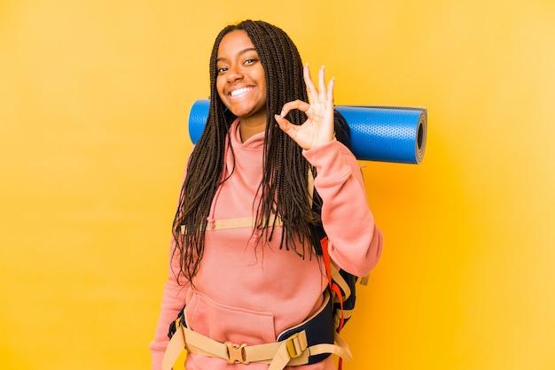 La mujer joven del backpacker del afroamericano aisló alegre y confiado que mostraba gesto aceptable.