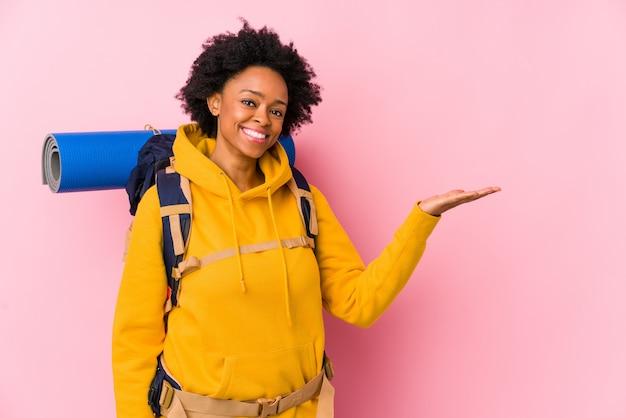 La mujer joven del backpacker del afroamericano aisló mostrar un espacio de la copia en una palma y sostener otra mano en la cintura.