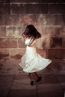 Mujer joven bailando en la calle por la noche