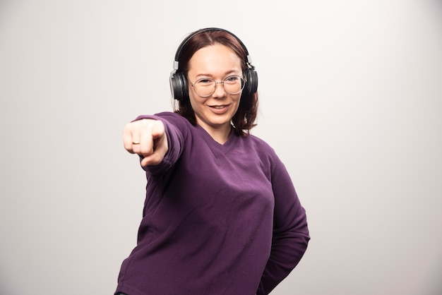 Mujer joven bailando y escuchando música en auriculares sobre un fondo blanco. foto de alta calidad