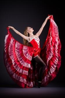 Mujer joven bailando en vestido rojo