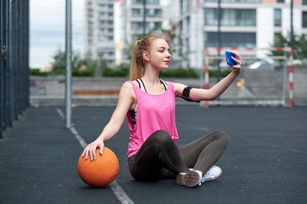 Mujer joven con baloncesto usando el teléfono después del entrenamiento, haciendo selfie