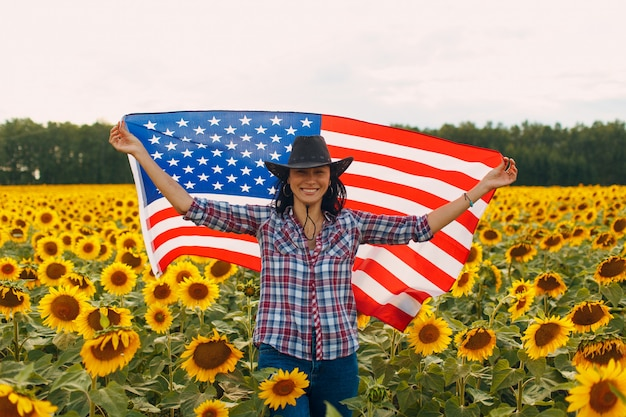 Mujer joven con bandera americana en el campo de girasol