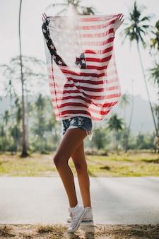 Mujer joven con bandera de estados unidos en tropical street