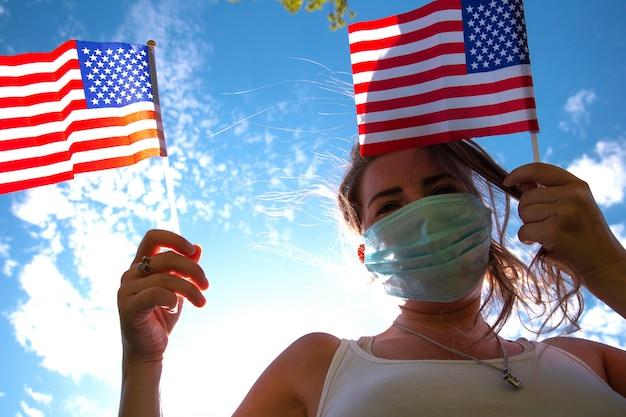 Mujer joven con bandera estadounidense en el cielo azul con luz solar y máscara de seguridad para covid-19 saludando a estados unidos
