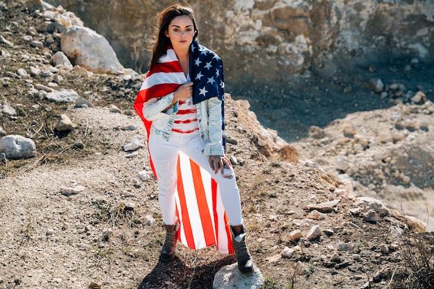Mujer joven en bandera de pie en la montaña