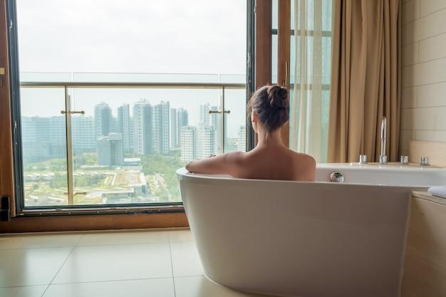 Mujer joven en baño blanco en baño de lujo con vista a la ciudad
