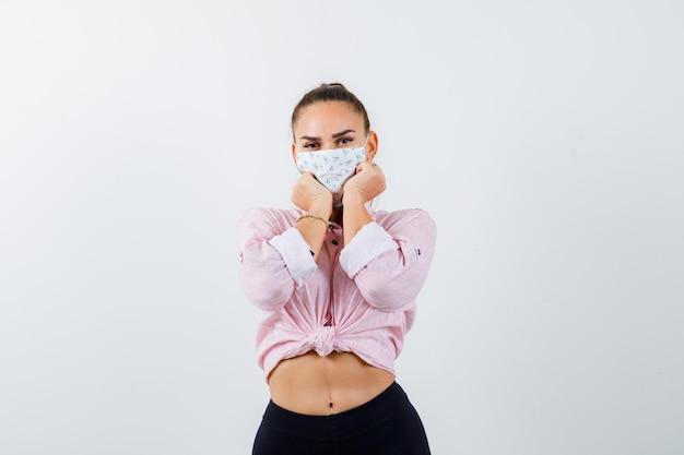Mujer joven con la barbilla apoyada en los puños en camisa, pantalones, máscara médica y luciendo linda, vista frontal.