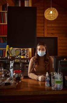 Mujer joven barista con máscara médica protectora y de pie detrás de la barra en un café de madera