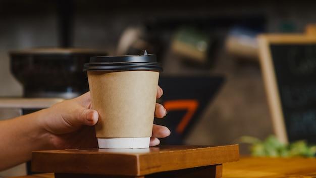 Mujer joven barista que sirve para llevar taza de papel de café caliente al consumidor de pie detrás de la barra de bar en el café restaurante.