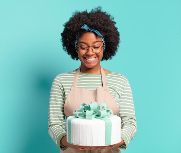 Mujer joven bastante afro panadero con un pastel de cumpleaños