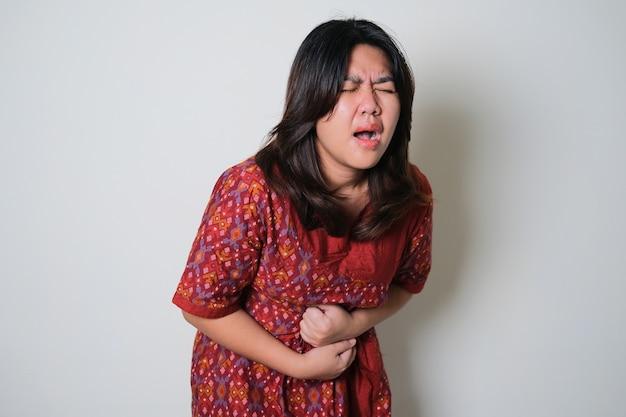Mujer joven bastante asiática que siente dolor durante el período de menstruación