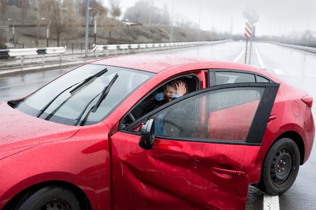 Mujer joven bastante asustada en el coche sintiéndose mal después de tener un accidente automovilístico