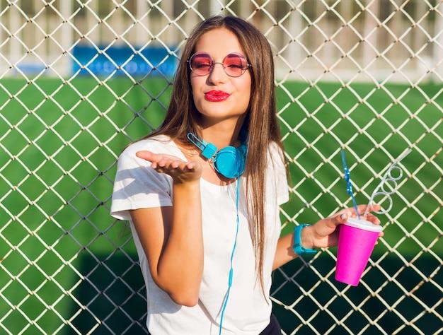 Mujer joven bastante encantadora hipster posando con taza de jugo saludable, escuchando música favorita