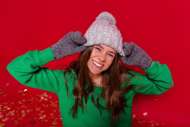 Mujer joven bastante encantadora en la pared roja en traje de invierno