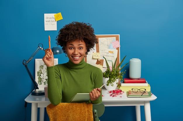 Mujer joven bastante rizada escribe notas o resumen, sostiene el bloc de notas y el bolígrafo, se prepara para la prueba, sesión o examen, disfruta estudiando y trabajando