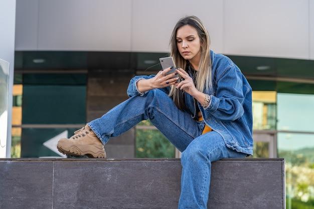 Mujer joven bastante rubia que mira el teléfono inteligente sentado fuera de la oficina. fotografía horizontal