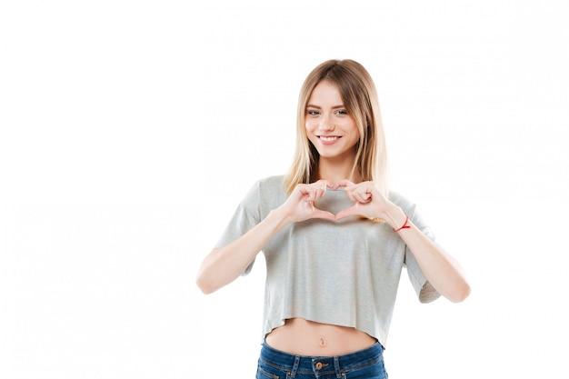 Mujer joven bastante sonriente que muestra gesto del corazón con dos manos