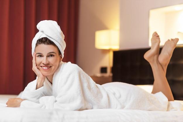 Mujer joven en bata de baño acostada en la habitación del hotel, relajada después de tomar un baño