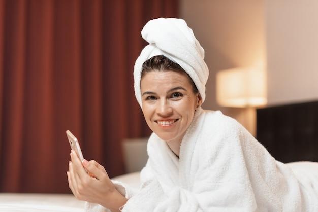 Mujer joven en bata de baño acostada en una habitación de hotel usando un teléfono móvil, relajada después de tomar un baño