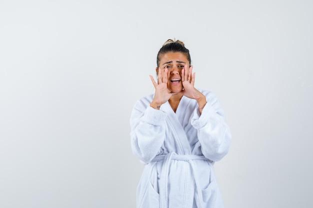 Mujer joven en bata de baño gritando algo y mirando preocupado