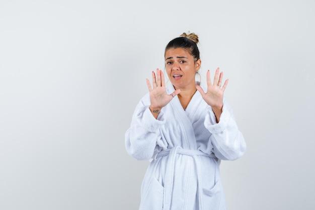Mujer joven en bata de baño mostrando señales de alto y mirando asustado