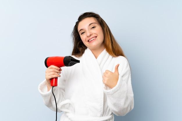 Mujer joven en una bata de baño con secador de pelo con los pulgares hacia arriba porque algo bueno ha sucedido