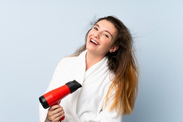 Mujer joven en una bata de baño con secador de pelo