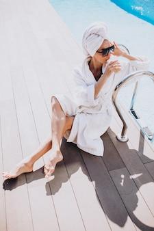 Mujer joven en bata de baño tomando café en la piscina