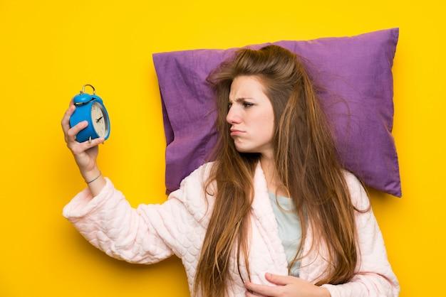 Mujer joven en bata en una cama estresada con reloj vintage