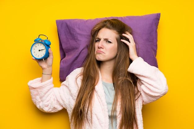 Mujer joven en bata en una cama estresada sosteniendo reloj vintage