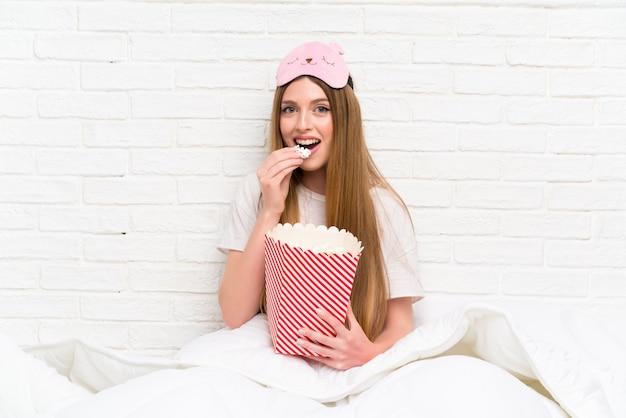 Mujer joven en bata en la cama con palomitas de maíz