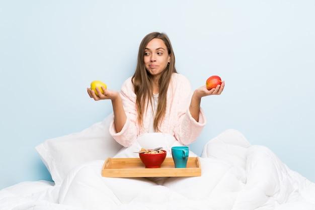 Mujer joven en bata con desayuno con una manzana