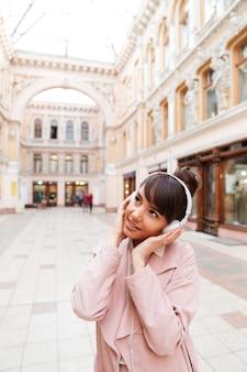 Mujer joven en bata rosa escuchando música con auriculares afuera