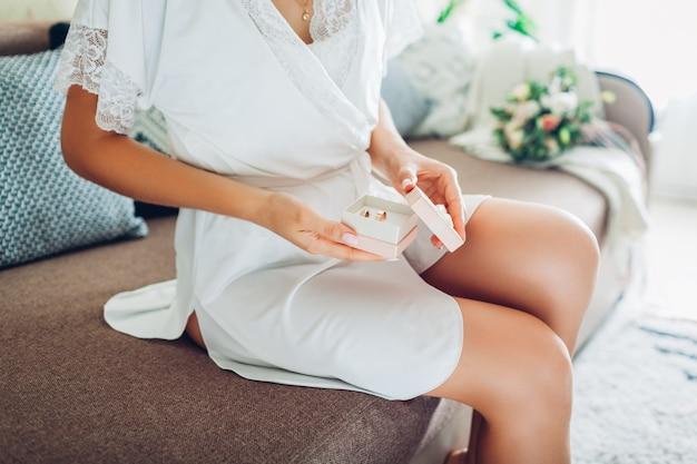 Mujer joven con bata de seda y caja con anillos en casa, novia el día de la boda