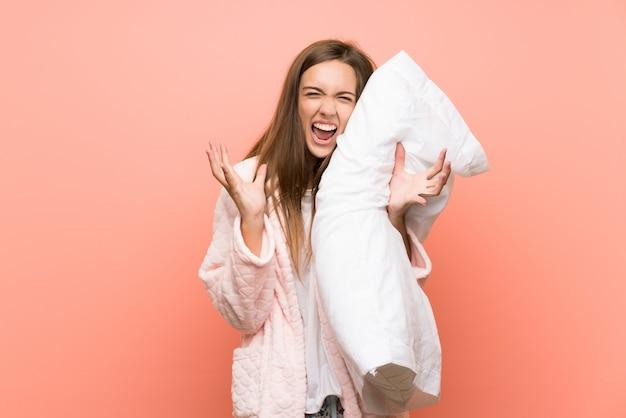 Mujer joven en bata sobre pared rosa infeliz y frustrada con algo