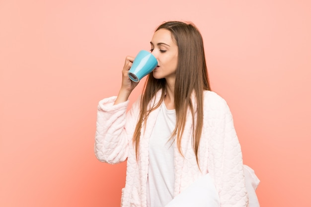 Mujer joven en bata sobre pared rosa sosteniendo una taza de café