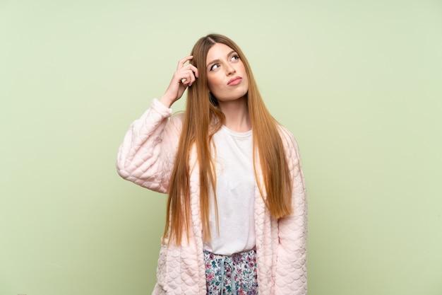 Mujer joven en bata sobre pared verde con dudas y con expresión de la cara confusa