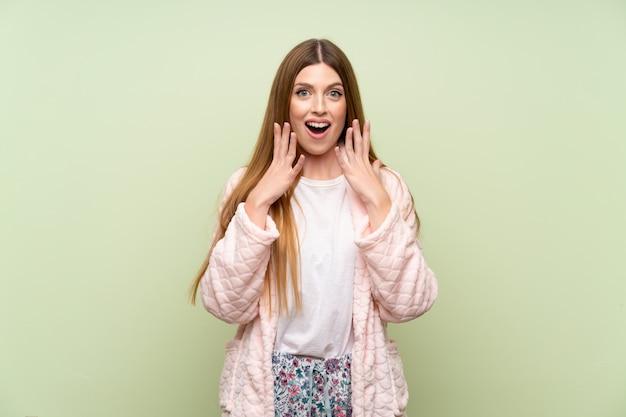 Mujer joven en bata sobre pared verde con expresión facial sorpresa