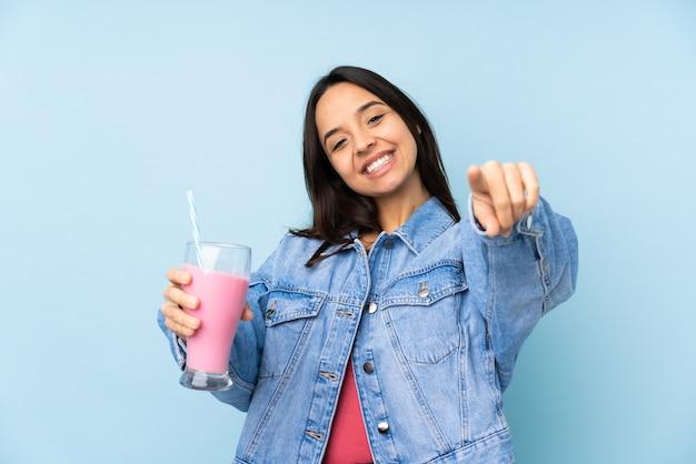 Mujer joven con batido de fresa señala con el dedo mientras sonríe