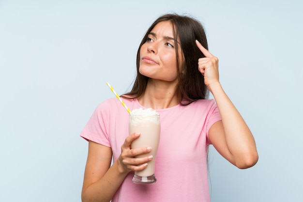 Mujer joven con batido de fresa sobre pared azul aislada con dudas y con expresión de la cara confusa