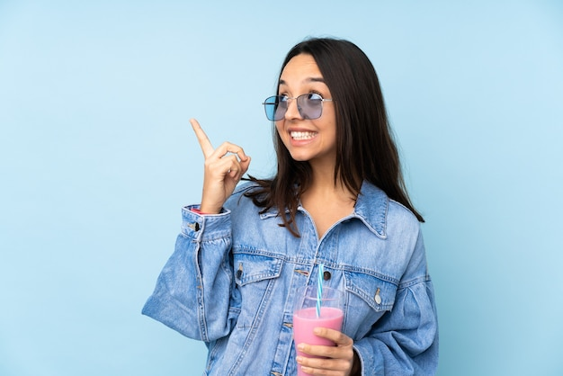 Mujer joven con batido de fresa sobre pared azul aislada señalando con el dedo índice una gran idea