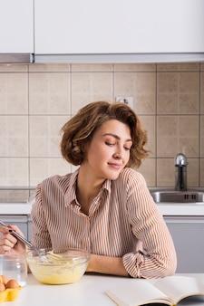 Mujer joven batiendo la yema de huevo en el recipiente de vidrio leyendo la receta en el libro