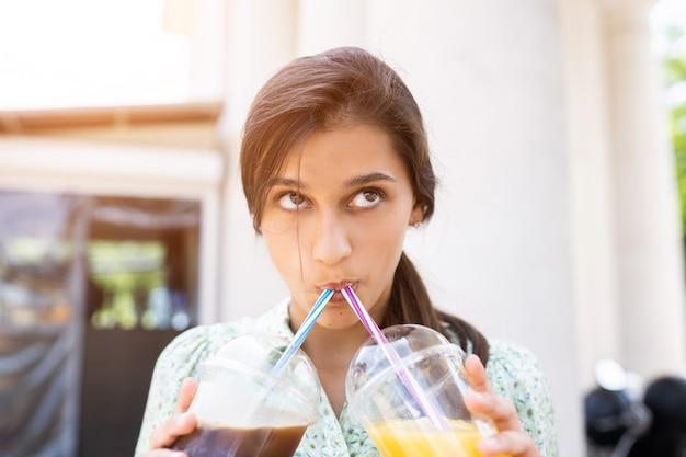 Mujer joven bebe dos cócteles con hielo en vasos de plástico con paja