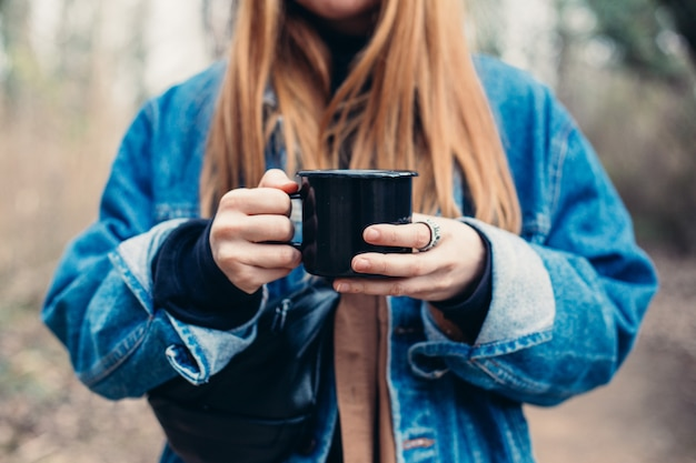 Mujer joven bebe taza de café en la orilla del lago