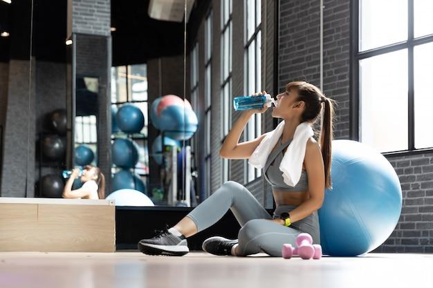 Mujer joven bebida asiática agua después de entrenamiento en una habitación