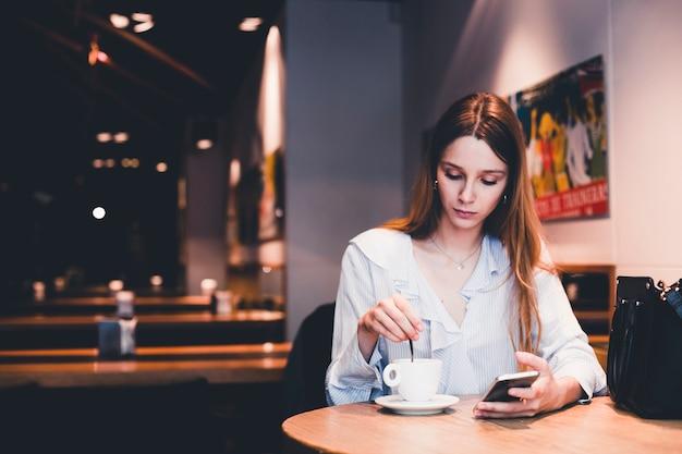 Mujer joven con bebida de mezcla de teléfono inteligente