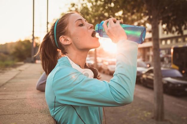 Mujer joven bebiendo agua después de hacer deporte